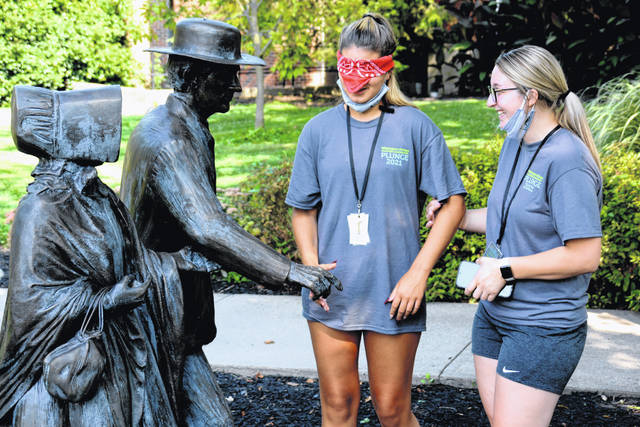 """<strong>SHAKING A HAND</strong>: Soon-to-be freshmen at Wilmington College participate in the Leadership Plunge Trust Walk, an exercise in which a peer leads a blindfolded student to iconic locations on campus. There, they learn about, in this case, the Isaac and Sarah Harvey statue, which depicts the local Quaker couple who personally petitioned President Lincoln to end slavery in the 1860s. """"Meeting"""" Isaac Harvey is Breanna Barnett of Wilmington, who is led by Delaney Weisend of Summerfield."""