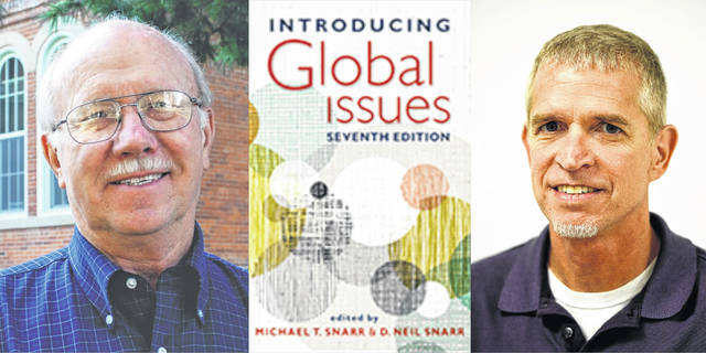"""Editors Neil Snarr, left, and Michael Snarr flank a copy of their new book, the seventh edition of """"Introducing Global Issues."""""""