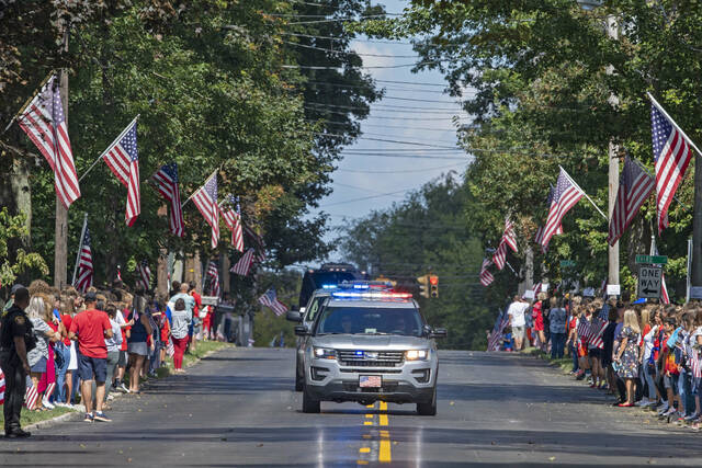 Ohio Highway Patrol cruiser lead the procession for Navy Corpsman Maxton Soviak as it makes its way to Morman-Hinman-Tanner Funeral Home, Wednesday, Sept. 8, 2021, in Berlin Heights, Ohio.  Soviak was one of 13 U.S. troops killed in a horrific suicide bombing at Afghanistan's Kabul airport on Aug. 26.  (AP Photo/David Dermer).