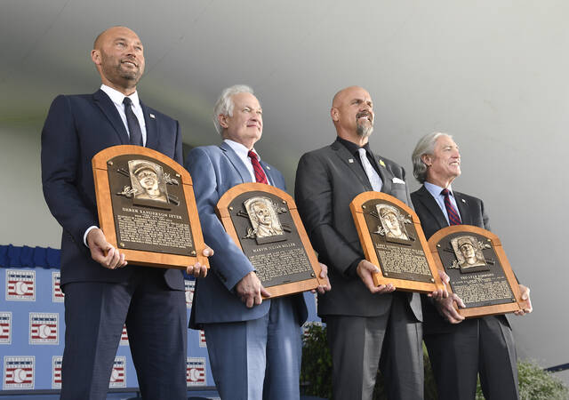 Hall of Fame inductees, from left, Derek Jeter, Donald Fehr accepting for the late Marvin Miller, Larry Walker and Ted Simmons hold their plaques for photos after the induction ceremony at Clark Sports Center on Wednesday, Sept. 8, 2021, at the National Baseball Hall of Fame in Cooperstown, N.Y. (AP Photo/Hans Pennink)