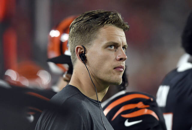 Cincinnati Bengals quarterback Joe Burrow (9) watches from the sidelines during the first half of an NFL preseason football game against the Tampa Bay Buccaneers Saturday, Aug. 14, 2021, in Tampa, Fla. (AP Photo/Jason Behnken)