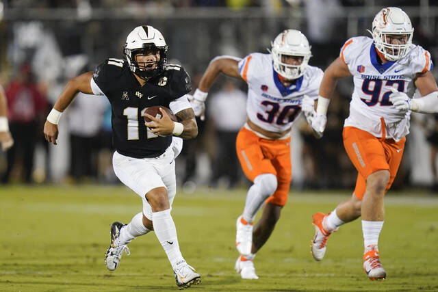Central Florida quarterback Dillon Gabriel, left, runs for yardage past Boise State defensive end Isaiah Bagnah (30) and defensive tackle Michael Callahan (92) during the first half of an NCAA college football game Thursday, Sept. 2, 2021, in Orlando, Fla. (AP Photo/John Raoux)