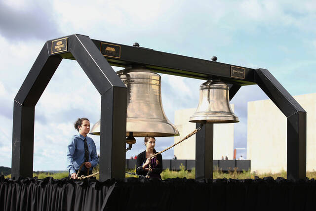 FILE - Matthew Prosser and Gina Rhoads of Shanksville-Stonycreek High School ring the Bells of Remembrance during the service of remembrance tribute to the passengers and crew of Flight 93 at the Flight 93 National Memorial in Shanksville, Pa, Sunday, Sept. 11, 2016, as the nation marks the 15th anniversary of the Sept. 11 attacks. (AP Photo/Jared Wickerham, File)