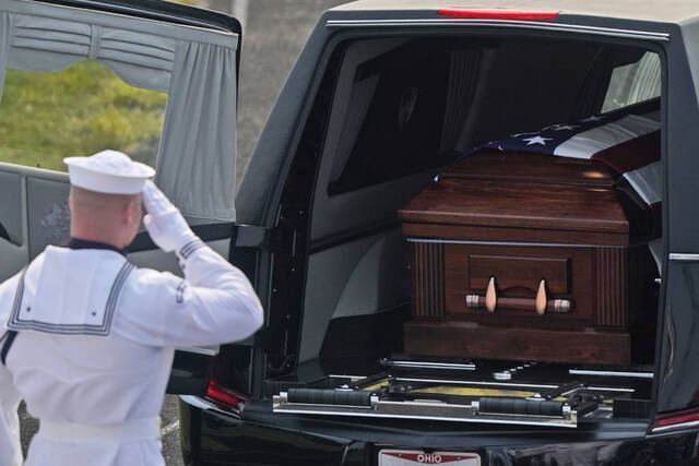 A member of the U.S. Navy Honor Guard gives a final salute to Navy Corpsman Maxton Soviak at Edison High School Stadium, Monday, Sept. 13, 2021, in Milan, Ohio. Soviak was one of 13 U.S. troops killed in a suicide bombing at Afghanistan's Kabul airport on Aug. 26. (AP Photo/Tony Dejak)