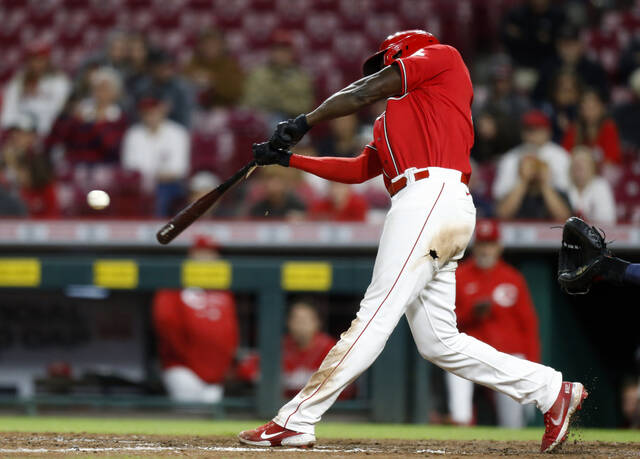 Cincinnati Reds' Aristides Aquino hits a RBI single to win the game against Washington Nationals pitcher Mason Thompson during the 11th inning of a baseball game in Cincinnati, Friday, Sept. 24, 2021. The Reds won 8-7. (AP Photo/Paul Vernon)