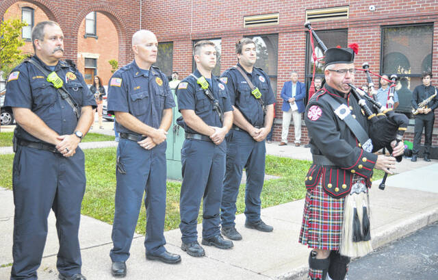 Former Wilmington firefighter Ed Myers plays the bagpipes at the 9/11 commemoration Friday.