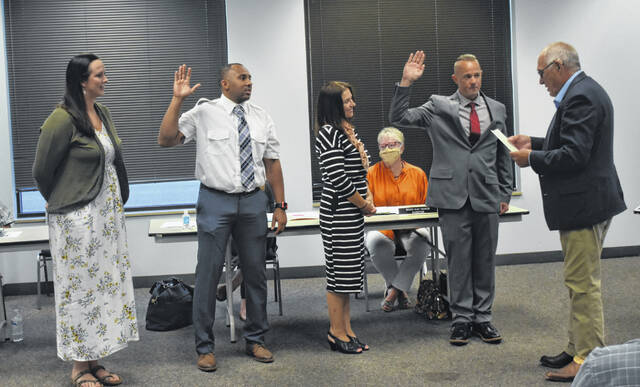 Mayor John Stanforth, far right, swears in Aaron Horak, second from right, and Marque Jones II, second from left, who are accompanied by their respective wives, as they're sworn in as Wilmington's newest firefighters at Thursday's Wilmington City Council meeting.