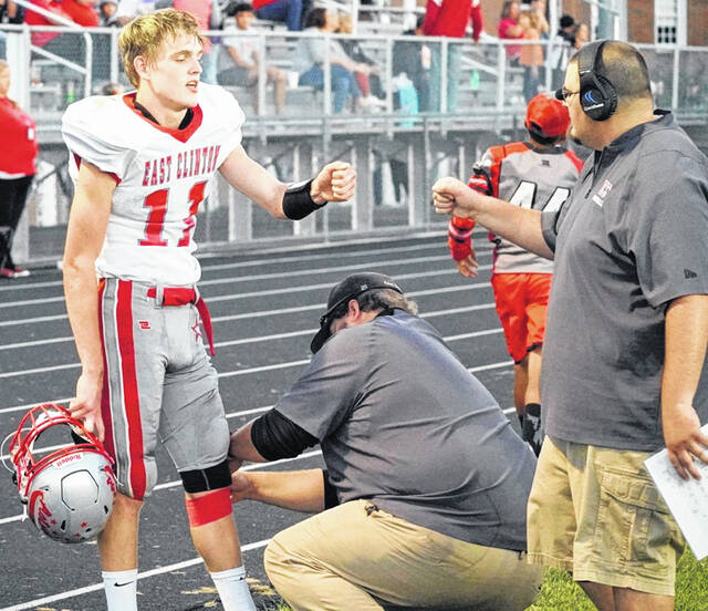 With a congratulations from head coach Steven Olds, East Clinton's Jared Smith (11) gets a tape job from an athletic trainer during last week's game with McClain