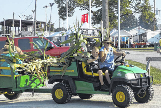 The driver and young passenger of a utility vehicle give friendly waves as they make their way Saturday on the county fairgrounds during the Corn Festival.