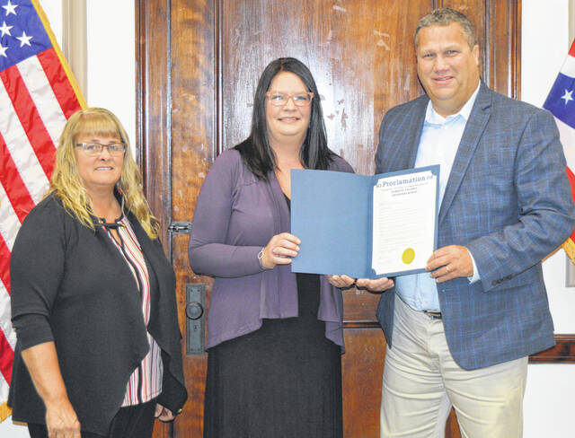 The Board of Clinton County Commissioners proclaim October as Domestic Violence Awareness Month. According to the wording in the proclamation, about one in three Americans have witnessed an incident of domestic violence. Pictured are, center, Dara Gullette of the local domestic violence agency, and Commissioners Brenda K. Woods and Mike McCarty.