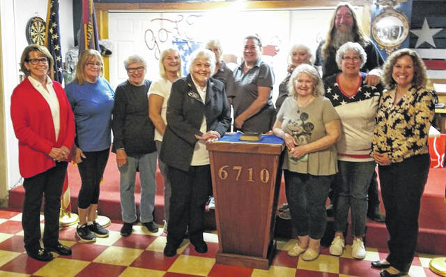 Shown are VFW Auxiliary members with District 4 Auxiliary Vice President Bev Acord (at far left) and President Annette Armacost (immediately left of the podium).