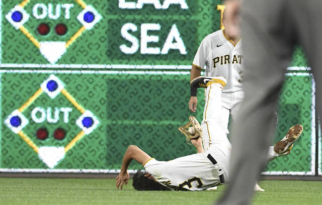 Pittsburgh Pirates' Cole Tucker (3) makes a diving catch for an out in the seventh inning against the Cincinnati Reds during a baseball game in Pittsburgh, Friday, Oct. 1, 2021. (AP Photo/Philip G. Pavely)