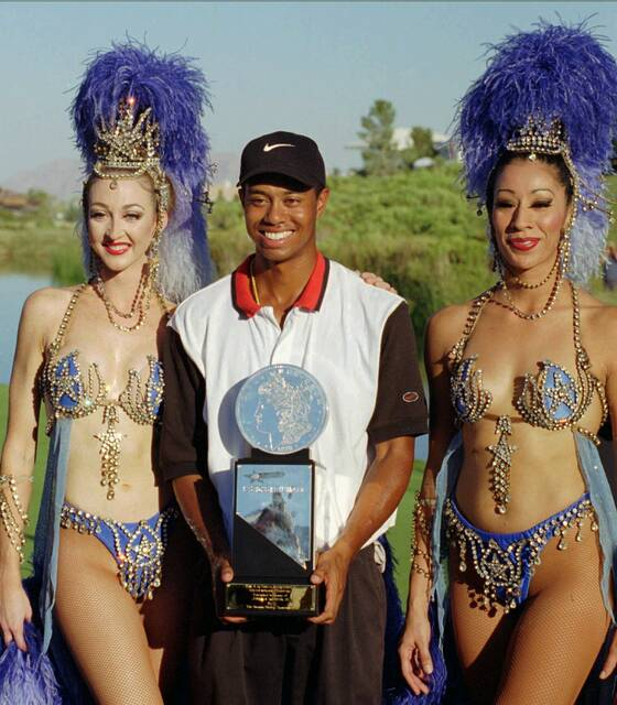 FILE - In this Oct. 6, 1996, file photo, Tiger Woods, center, poses with Ballys' Jubilee dancers Windi See, left, and Gracie Martinez after winning his first pro golf tournament at the Las Vegas Invitational in Las Vegas. Twenty-five years ago this week Woods won for the first time on the PGA Tour at the Las Vegas Invitational, changing golf forever. (AP Photo/Lennox McLendon, File)