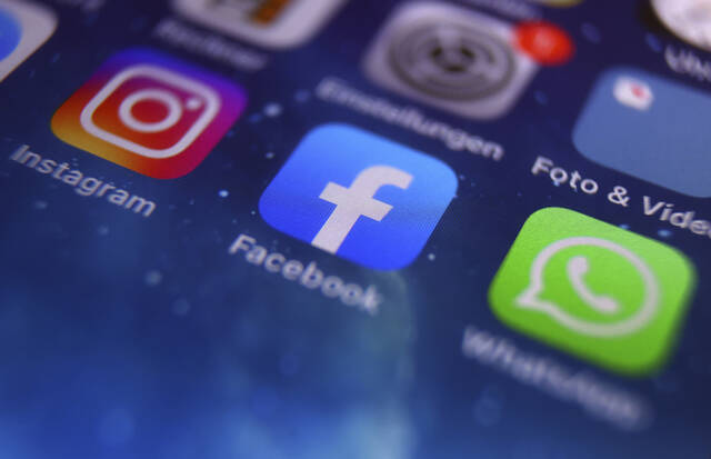 The icons of Instagram, Facebook and WhatsApp can be seen on the screen of a smartphone in Kempten, Germany, Monday, Oct. 4, 2021. The six-hour outage of Facebook, Instagram and Whatsapp on Monday was a headache for many casual users. But the outage was far more serious for many people worldwide who rely on the social media sites to communicate with relatives, friends and neighbors and run their businesses. It's a stark reminder that many of the most popular ways to communicate are controlled by one company, Facebook. And any lengthy outage can have severe implications. (Karl-Josef Hildenbrand/dpa via AP)