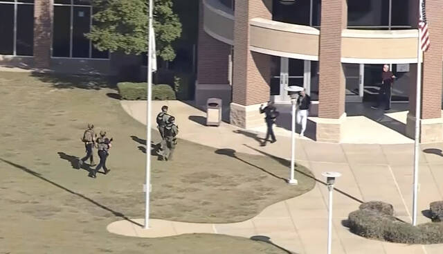 In this image from WFAA-TV video, law enforcement arrives at Timberview High School on Wednesday, Oct. 6, 2021 in Arlington, Texas. Authorities say a student opened fire inside the Dallas-area high school during a fight. (WFAA-TV via AP)