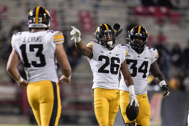 Iowa defensive back Kaevon Merriweather (26) reacts after making an interception on a pass from Maryland quarterback Taulia Tagovailoa, not visible, during the second half of an NCAA college football game, Friday, Oct. 1, 2021, in College Park, Md. Iowa defensive end Joe Evans (13) and linebacker Jay Higgins (34) look on. (AP Photo/Julio Cortez)