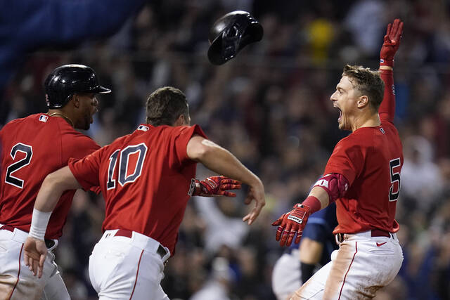 Boston Red Sox Enrique Hernandez, right, celebrates with teammates after hitting a sacrifice fly ball to score Danny Santana to beat the Tampa Bay Rays in the ninth inning during Game 4 of a baseball American League Division Series, Monday, Oct. 11, 2021, in Boston. The Red Sox won 6-5. (AP Photo/Charles Krupa)