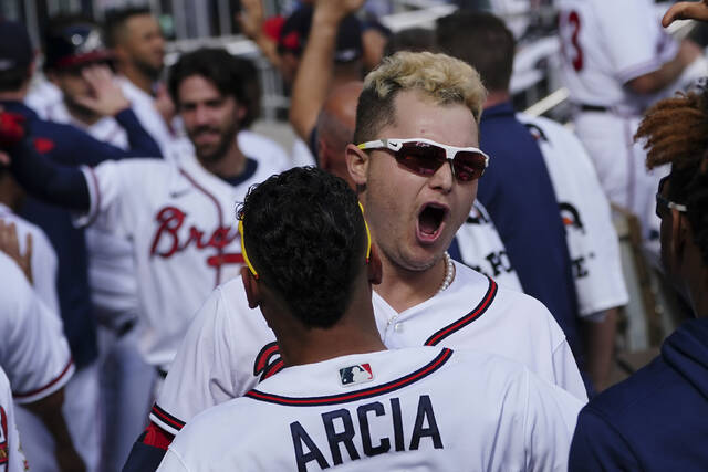 Atlanta Braves' Joc Pederson (22) celebrates his three-run homer in the dugout against the Milwaukee Brewers during the fifth inning of Game 3 of a baseball National League Division Series, Monday, Oct. 11, 2021, in Atlanta. (AP Photo/John Bazemore)