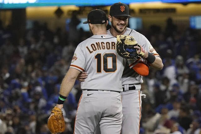 San Francisco Giants' Evan Longoria (10) hugs teammate Kris Bryant, right, after Longoria's solo home run gave the the Giants a 1-0 win over the Los Angeles Dodgers in Game 3 of a baseball National League Division Series, Monday, Oct. 11, 2021, in Los Angeles. (AP Photo/Marcio Sanchez)