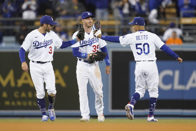 Los Angeles Dodgers' Chris Taylor (3), Cody Bellinger (35) and Mookie Betts (50) celebrate after the Dodgers defeated the San Francisco Giants 7-2 in Game 4 of a baseball National League Division Series, Tuesday, Oct. 12, 2021, in Los Angeles. (AP Photo/Ashley Landis)