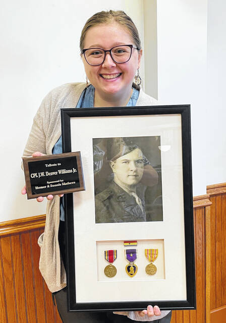 Clinton County History Center Director Shelby Boatman holds the completed tribute plaque and frame with a photo and service medals posthumously awarded to J.W. Denver Williams Jr.