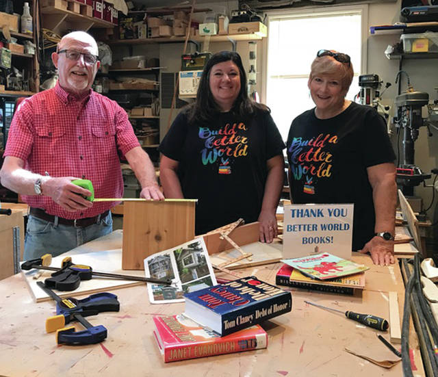 With the beginnings of the Little Free Library are, from left, Larry Dunbar, Martie Yunker and Cindy Vance.