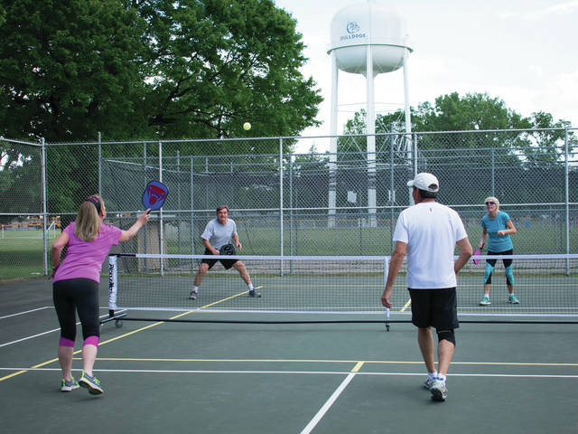 Lu Luce serves the ball to Bob Wertz and Patty Miller during a pickleball match last Monday.