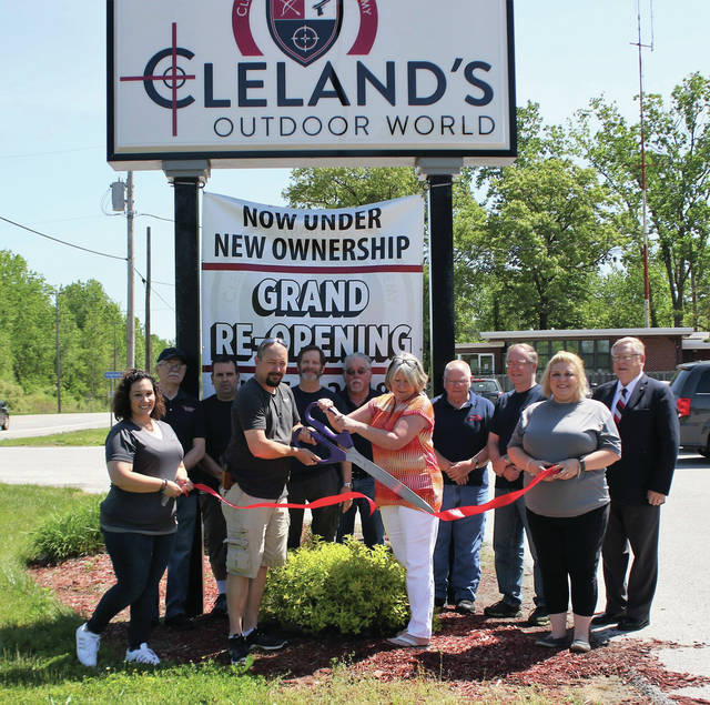 The new owners of Cleland's Outdoor World cut the ribbon at the business on Thursday.