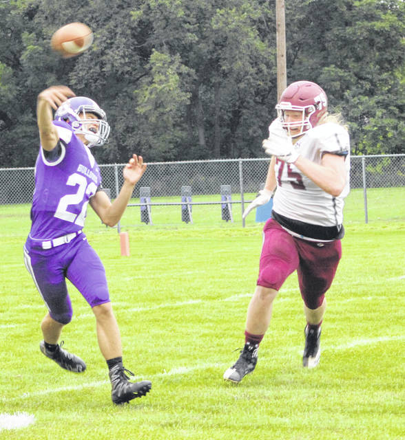 Swanton quarterback Dylan Gilsdorf passes as Rossford's Brett Deyarmond chases him Friday.