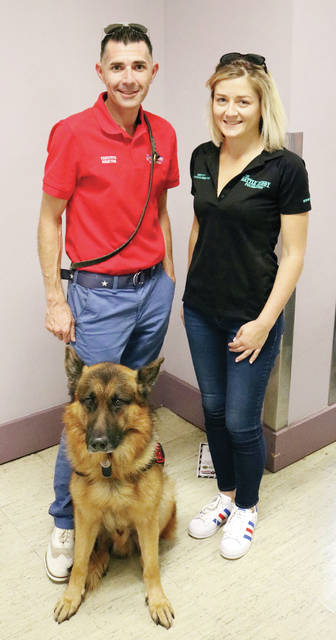Battle Buddy Foundation co-founders Kenny Bass and Chrissy Faulkner with service dog Atlas.