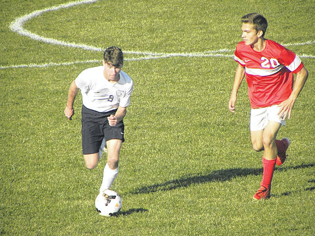 Swanton's Zach Schaller advances the ball up the field as Jacob Hageman (20) approaches for Wauseon during Thursday's game. The Bulldogs and Indians played to a 1-1 tie.