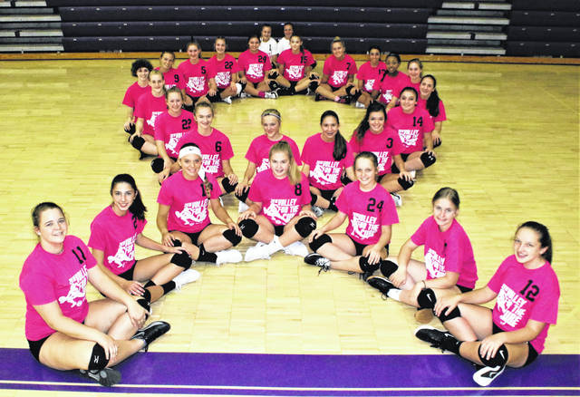 The Swanton volleyball team forms the Pink Ribbon Breast Cancer Logo.