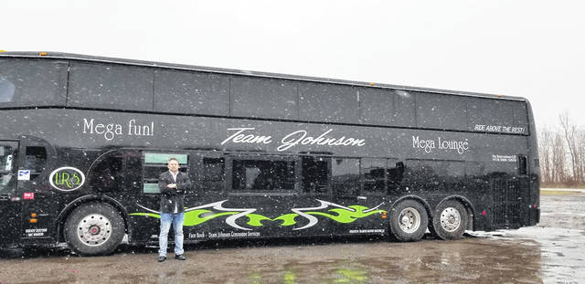 Brandon Johnson stands in front of his double-decker bus.