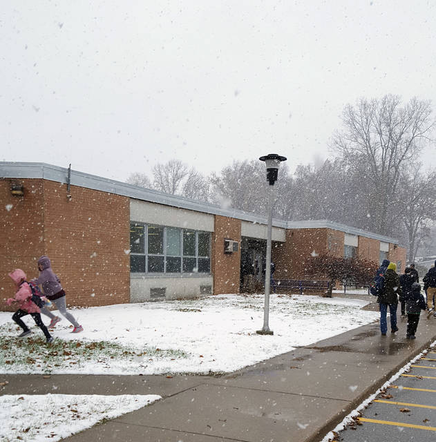 A light snow fell much of the day Thursday in the Swanton area as the chilly November weather continued. Above, students run through snowflakes as the school day ends at Swanton Elementary School.