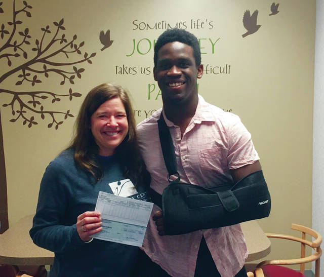 Swanton High School senior Xavier Williams recently donated the money raised during a pink out football game he organized in October. He recently presented donations to The Victory Center, above, and Baskets of Care.