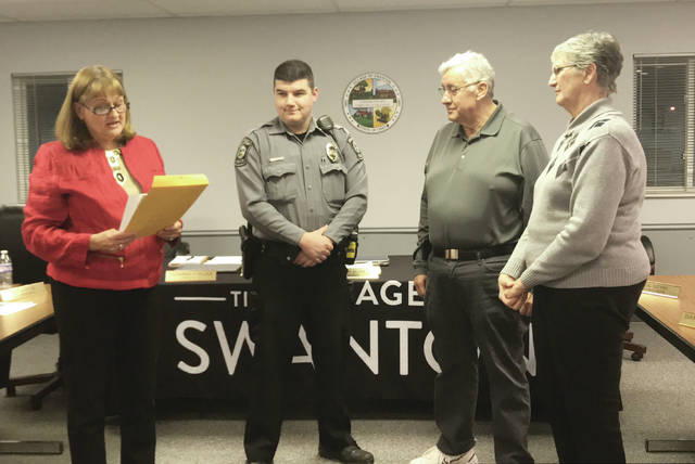 Swanton Mayor Ann Roth recounts officer Lee Kusz's effort in helping to save the life of Robert DeVries, while Carol DeVries also looks on.