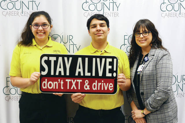"In an effort to help keep students safe at Four County Career Center in Archbold, the University of Toledo Medical Center recently donated ""STAY ALIVE! don't TXT & drive"" signs and banners to be posted at the school and given to students to display. Shown presenting a banner to Career Center Law Enforcement and Security Tactics students Mia Beltran and Adam Rohrs is Angela Castillo, UTMC trauma/injury prevention coordinator."