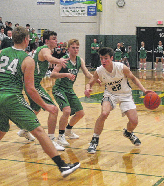 Mason Loeffler of Evergreen dribbles the ball between a host of Delta defenders during a non-league contest this season. He was recently named honorable mention All-Ohio in Division III.