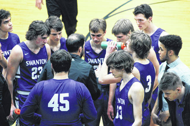 Swanton coach Joel Visser talks strategy with the Bulldogs during their game against Evergreen on Friday.