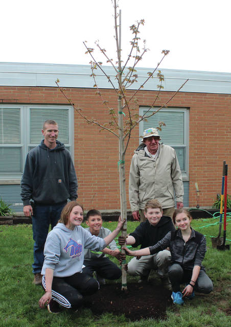 Swanton Middle School students Ava Keiser, Jalen Carrizales, Mason Hutchinson and Aurora Young planted a tree with Swanton Tree Commission members Jim Lammon, left, and Walt Lange at the school Friday.
