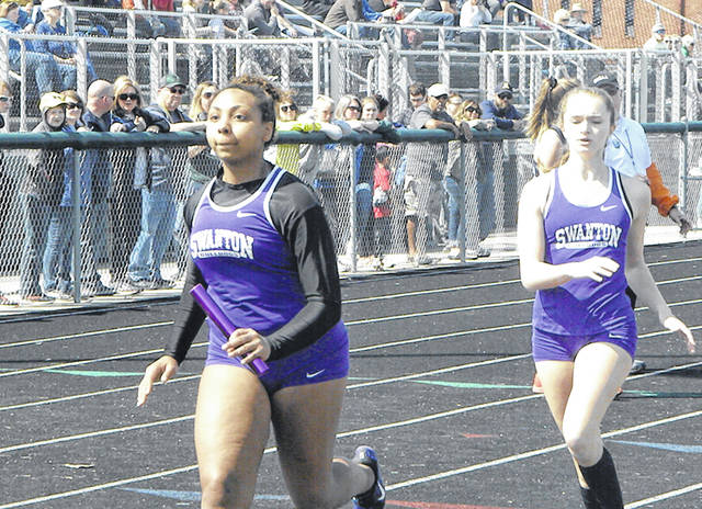 Ashlynn Waddell of Swanton, left, after getting the baton from Brooke Dockery in a relay at the Bob Eisenhart Invitational at Tinora Saturday. The Bulldog girls finished runner-up to Archbold and just three points behind the Blue Streaks.