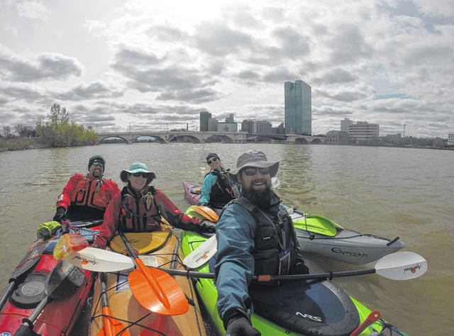 During their trip over the length of the Maumee River, from left, Bill Hoefflin, Amanda Domalski, Christina Seiler, and Paul Fuzinski stop for a photo near Downtown Toledo.