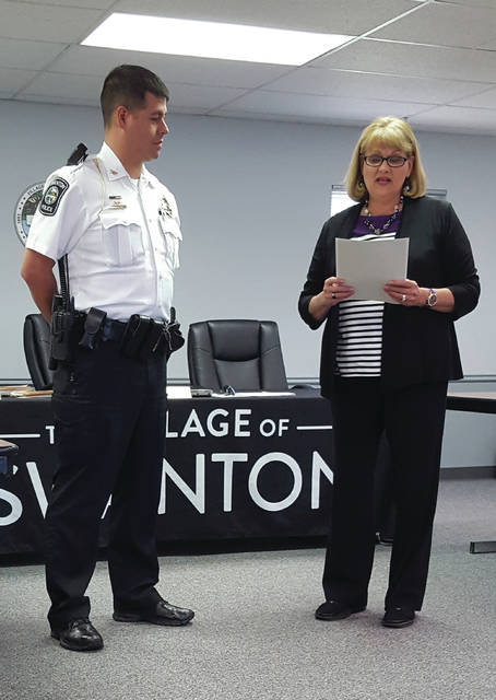 Mayor Ann Roth reads a proclamation of Police Week in the village, as Chief Adam Bergs stands near.
