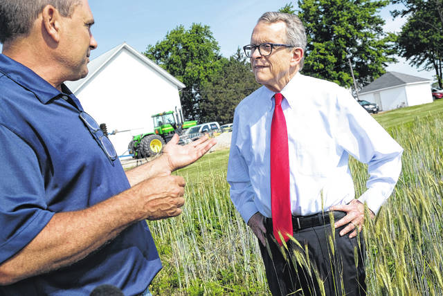 Oho Gov. Mike DeWine (right) speaks with local farmer Kris Swartz at his farm along Reitz Road in Perrysburg Township Wednesday morning. Visit www.sent-trib.com to watch a video.