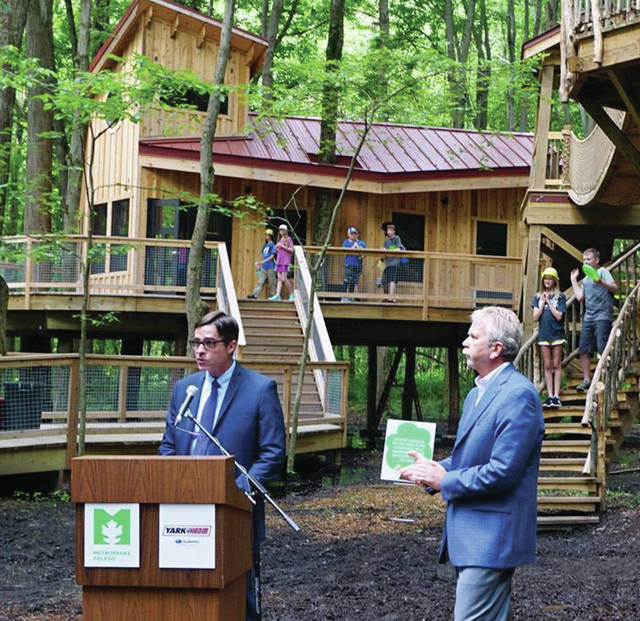Scott J. Savage, president of the Board of Park Commissioners, and John Yark of Yark Subaru, speak during a news conference at the Cannaley Treehouse Village June 18.