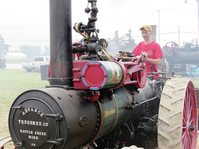 C.J. Holden of Doylestown, Pa., fires up his father's Advance thresher amidst the smoky atmosphere around him at a recent Threshers Reunion at the Fulton County Fairgrounds.