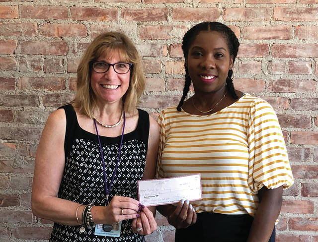 Fancy Moreland, , creator of Toledo Night Market, presents a donation check to Cheryl Rothschild, Director of Volunteers and Library Outreach at Read for Literacy.