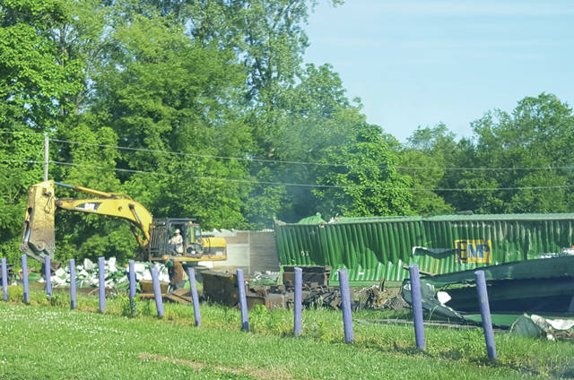 Above, a crew works Monday on the container cars that were moved to the Swanton High School practice football field following the derailment on June 6.