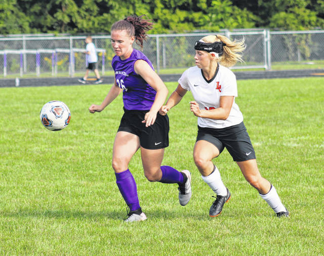Gaby Kosier of Swanton, left, tries to stave off Samantha Engler of Liberty Center for a loose ball during Tuesday's NWOAL soccer match. The Bulldogs fell to the Tigers 5-3.