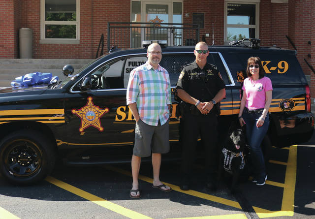 Last Saturday, the winning keys to the 2019 Chevy Tahoe were turned over to Justin Galbraith and Fazzo by Sandy Marcal of Vested Interest in K9s. The photo submitted in the contest was taken by David Bliss of Wauseon and entered by Deputy Galbraith back in 2018. Thirty different law enforcement departments throughout the United States entered the contest by submitting a photo. Pictured are Bliss, Galbraith and Fazzo, and Marcal.